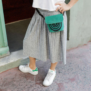 A woman wearing a green waxed canvas fanny pack around her waist - Devrim Studio