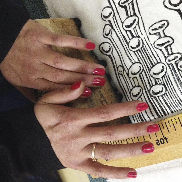 A woman block printing the artwork onto fabric - Devrim Studio