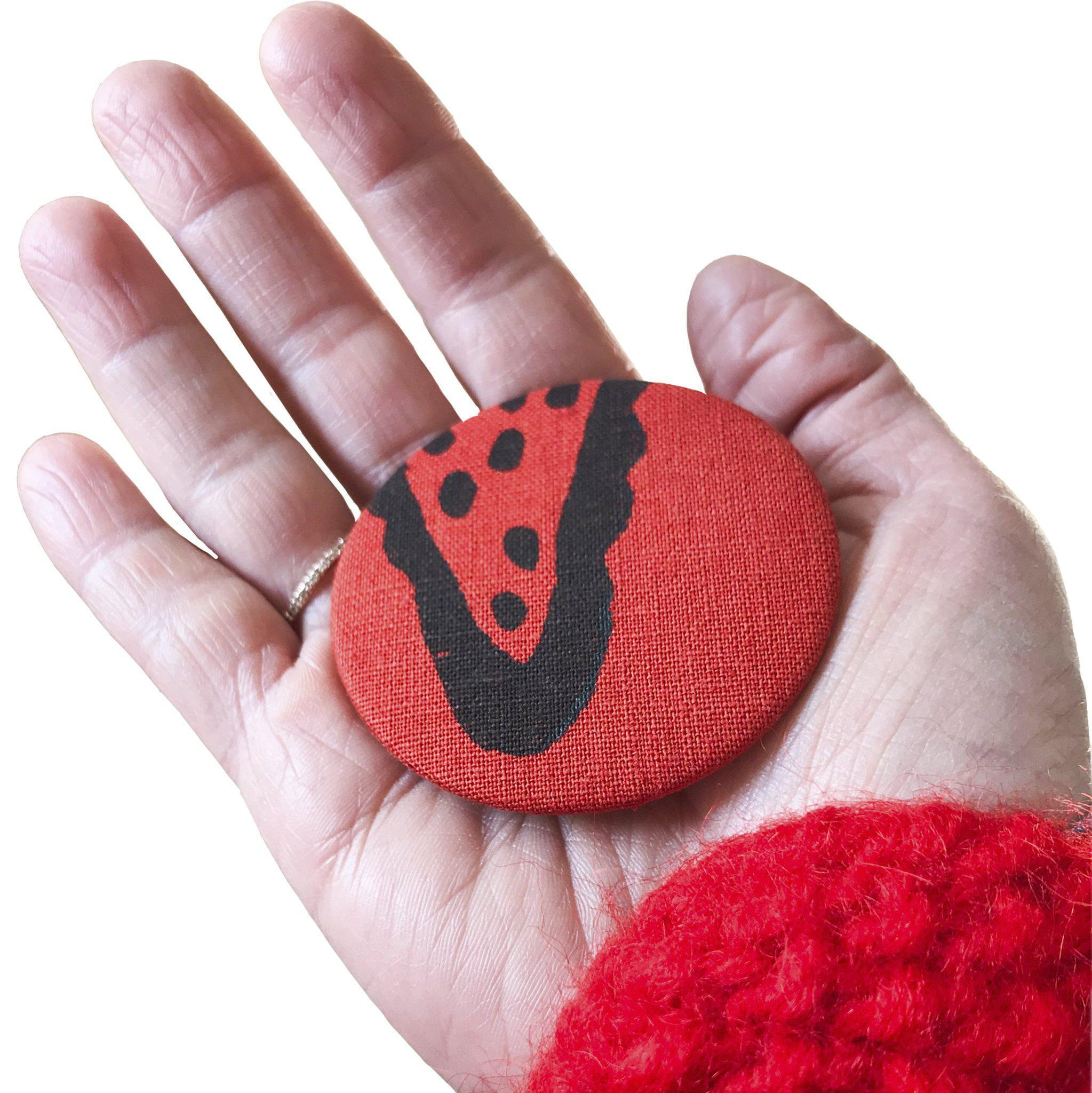 A hand holding a red 'Corn' magnet, bottle opener - Devrim Studio