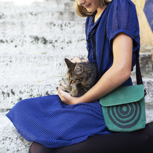 A woman wearing a green 'Time' shoulder bag and holding a cat-Devrim Studio