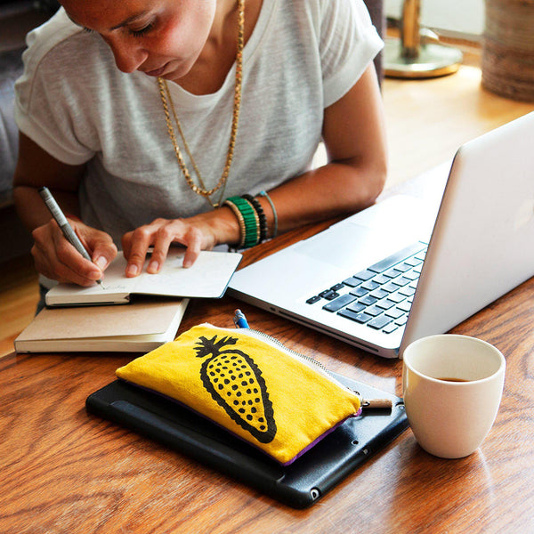 A woman working in her office with yellow pencil pouch and computer - Devrim Studio