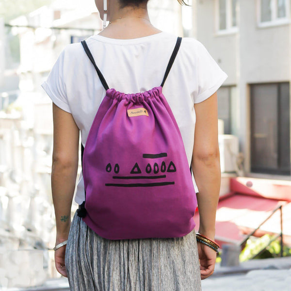 A woman wearing a purple bucket backpack - Devrim Studio