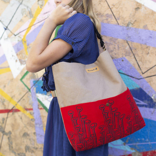 A woman holding a beige and red 'Stuck To The Floor' shoulder bag, crossbody bag - Devrim Studio