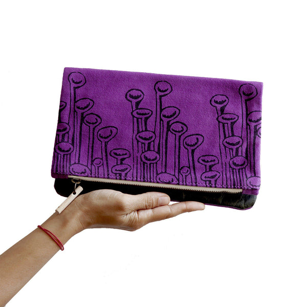 A woman holding a purple 'Stuck to the Floor' clutch, shoulder bag -Devrim Studio