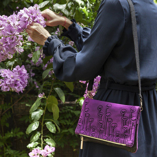 A woman wearing a purple 'Stuck to the Floor' clutch, shoulder bag -Devrim Studio