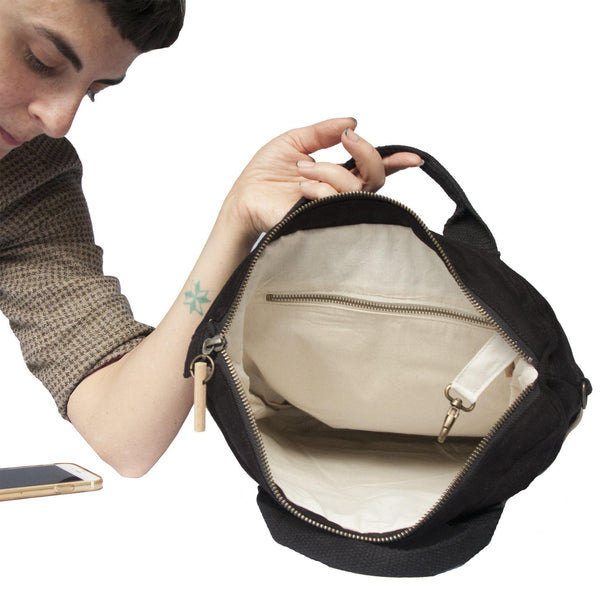 A woman showing the inside of the convertible backpack, crossbody, tote bag-Devrim Studio