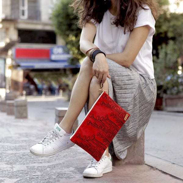 A woman holding a red 'Stuck to the floor' iPad sleeve, clutch from it's detachable wristlet- Devrim Studio