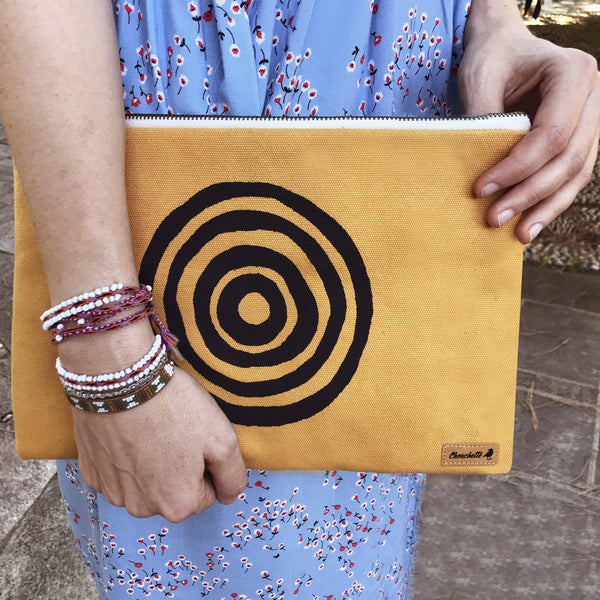 A woman holding a yellow 'Time' iPad sleeve, clutch - Devrim Studio