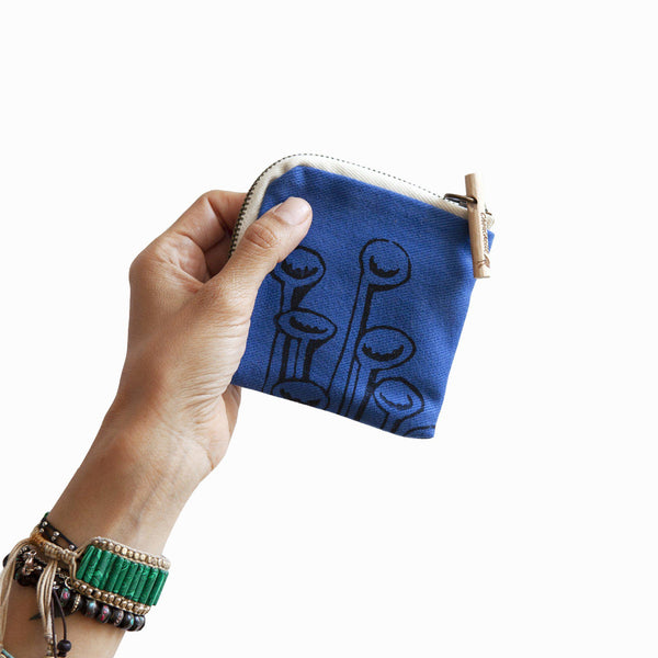 A woman holding a navy blue 'Stuck to the floor' wallet, purse - Devrim Studio