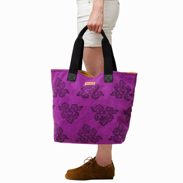 A woman holding a purple tote bag - Devrim Studio
