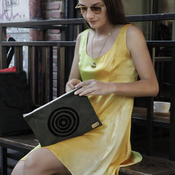 A woman holding a green 'Stuck to the Floor' waxed canvas iPad sleeve, clutch - Devrim Studio