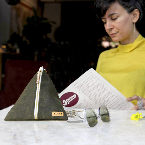 A woman sitting at a table to order food with her green Ursula Chain Purse - Devrim Studio