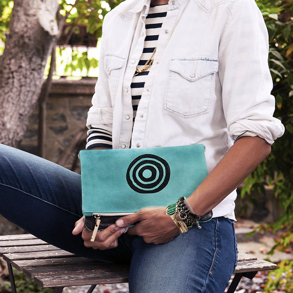 A woman holding a turquoise 'Time' shoulder bag that converts into a crossbody bag, or a fanny pack, or a clutch - Devrim Studio