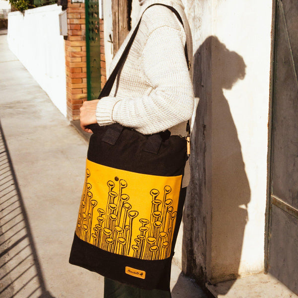 A woman wearing the yellow and black convertible backpack as a shoulder bag - Devrim Studio