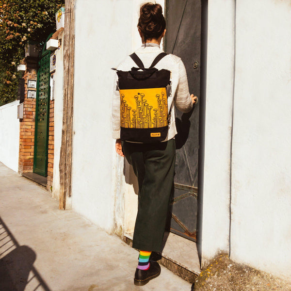 A woman wearing the yellow and black convertible backpack - Devrim Studio