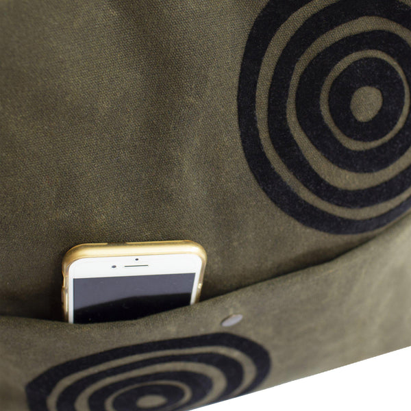 Detail view of the khaki green 'Time' waxed canvas shoulder bag with a cell phone inside it's front pocket - Devrim Studio