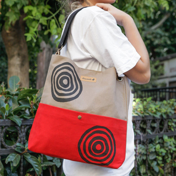A woman wearing a beige and red  canvas shoulder bag that converts into a crossbody bag - Devrim Studio