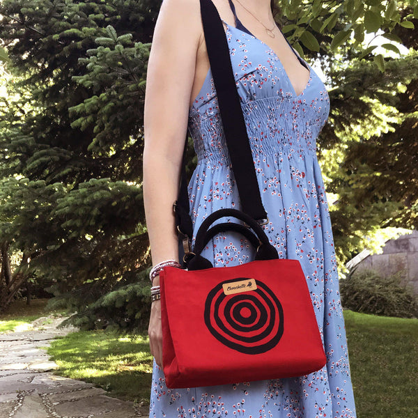 A woman wearing the red 'Time' Mini Tote Bag - Devrim Studio