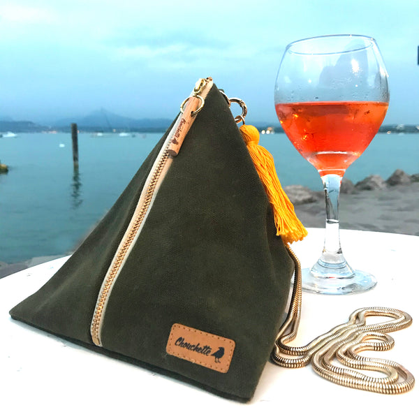 Waxed Canvas Ursula chain bag photographed on a table by the lake.