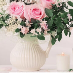 Pink roses in a white vase beside a natural soy candle