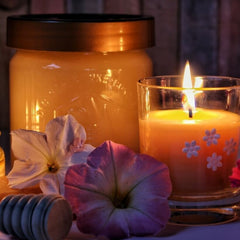 Soy candle beside flowers and honey pot