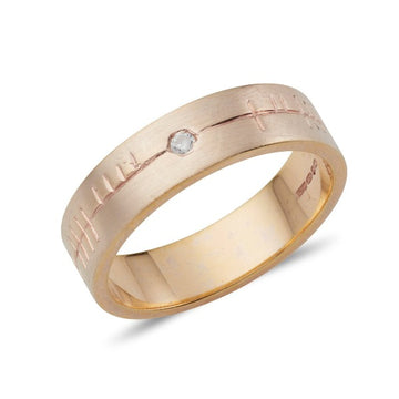 18ct rose gold flat 6mm wide wedding ring with a matt finish and ogham engraving, there is a small diamond at the centre of the ring