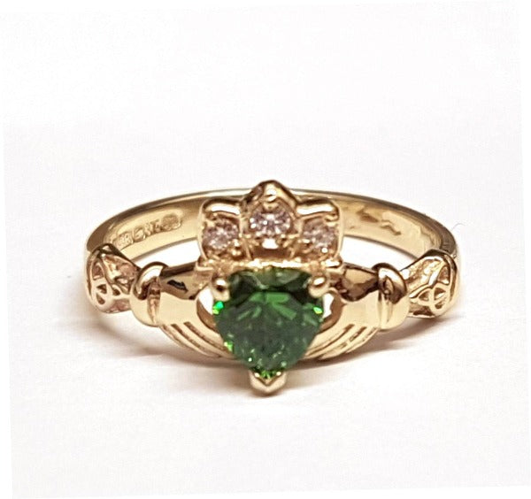 9ct yellow gold ladies birthstone claddagh ring with heart shaped stone in the centre and small round stones in the crown with green stone in the centre