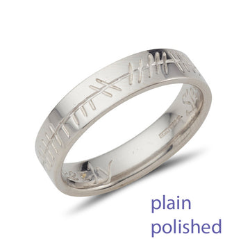 white gold easy it wedding band with a plain polished and curved inside,  it has an Ogham inscription on the outside of the band