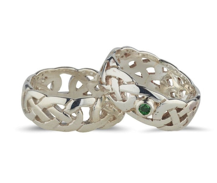 sterling silver celtic design rings with a fully pierced out celtic pattern, ideal for both male an female, they are 7.5mm wide one ring is set in the centre with a bezel set green cubic zirconia, the other ring has no stone