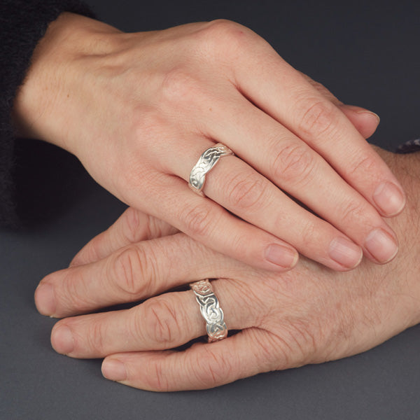 sterling silver celtic design matching his and hers rings, the pattern is embossed on the ring and the edges of the rings are wavy as shown on this womans and mans hands