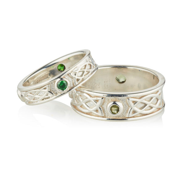 wite gold celtic design matching his and hers rings, they are set with 3 emeralds in each ring, the 3 stones are rubover or bezel set at north east and west points of the ring