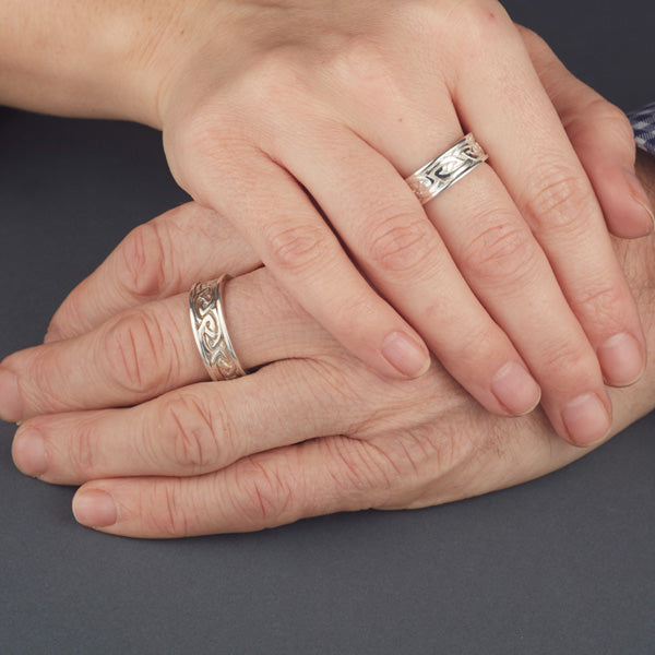white gold matching his and her wide celtic wedding ring set. the 2 celtic rings are solid and have plain straight rimms on each side  here the rings are shown on a ladies and gents hands
