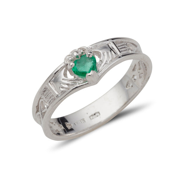 white gold wishbone shaped claddadg ring with a small heart shaped emerald set into claws