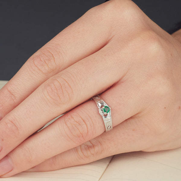 white gold wishbone shaped claddadg ring with a small heart shaped emerald set into claws as shown on a ladies finger