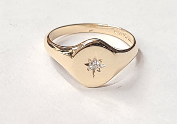 ladies gold signet ring set with a diamond