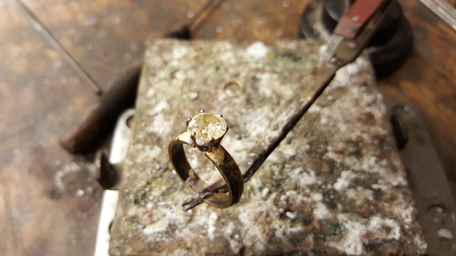 yellow gold ring with a pale yellow stone before it is been set