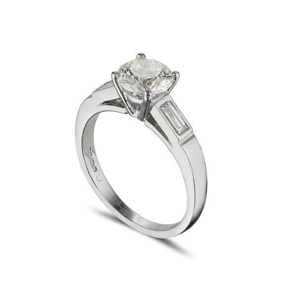 Platinum solitaire engagement ring with baguette diamonds set in the soulders on a chunky band