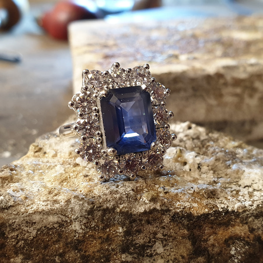 Platinum diamond and sapphire large classic style cluster ring, the sapphire is an ink blue colour and there is 12 20 point diamonds around the sapphire
