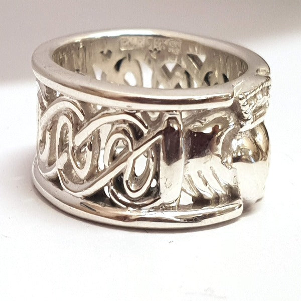 sterling silver 8mm wide calddagh band, there is a claddagh symbol in the centre of the ring with a pierced celtic design going around the ring, from the side view