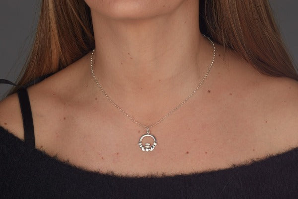 this shows the smaller claddagh charm on a necklace worn by a lady