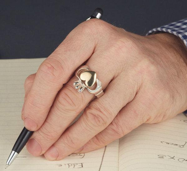sterling silver gents heavy solid claddagh ring with gold heart as shown on a mans hand