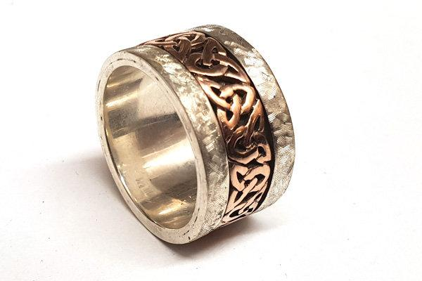 Sterling silver extra wide 12mm celtic design ring. the centre celtic design is in yellow gold with a black oxidized background, the rimms are approx each 2mm wide and have a hammered texture with a matt finish