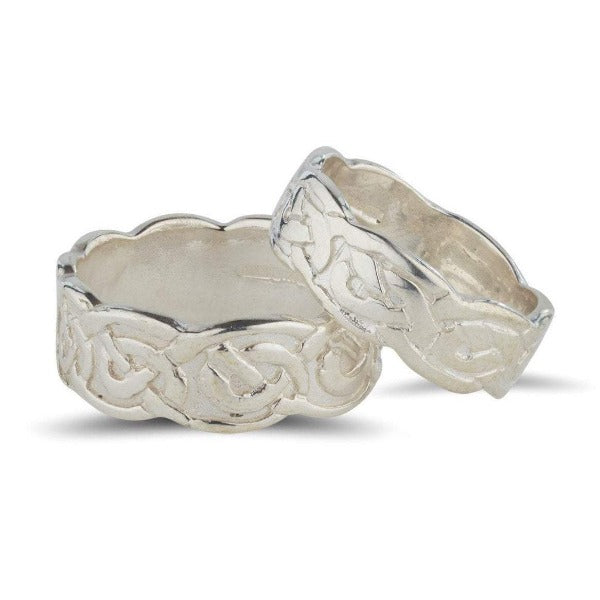 sterling silver celtic design matching his and hers rings, the pattern is embossed on the ring and the edges of the rings are wavy slightly wider