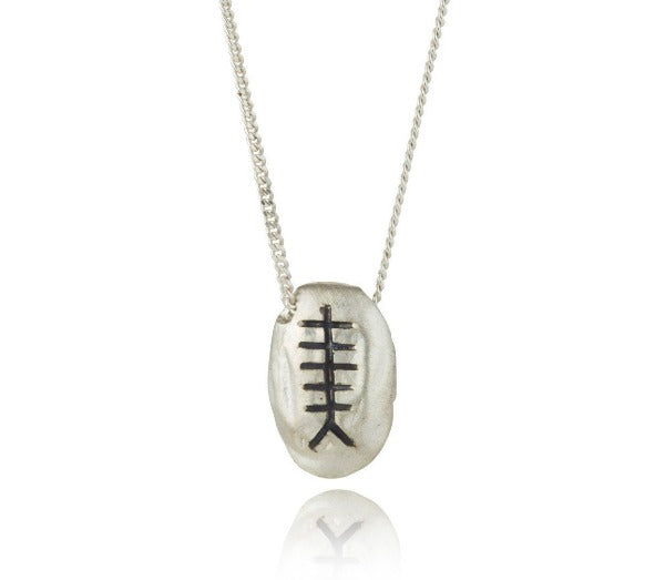 sterling silver pebble with chain going through the pendant,  they are then engraved with an ogham initial
