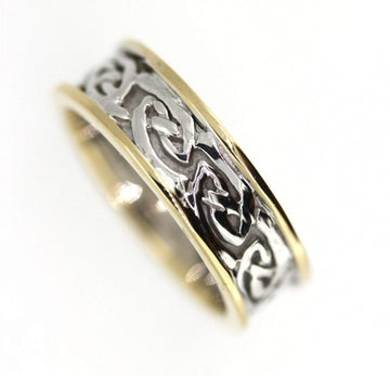 two tone celtic design ring with yellow gold rimms, the centre is silver celtic design pattern that is solid, the rimms are slightly raised