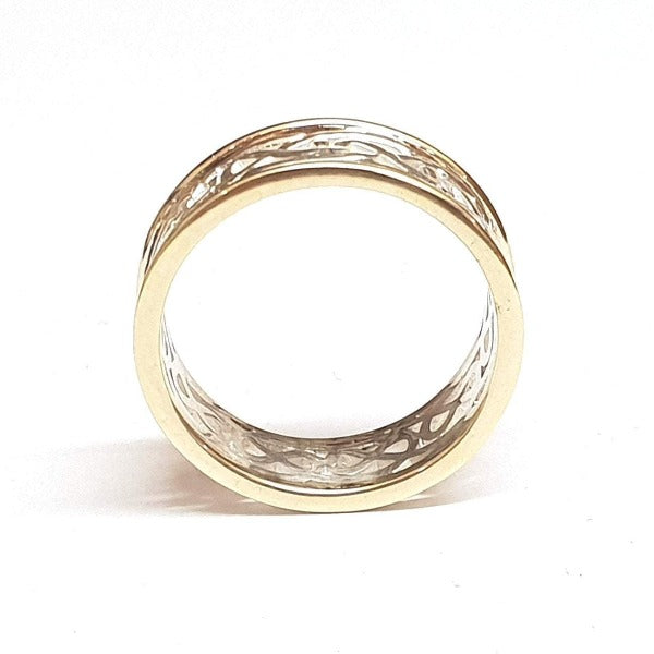 two tone celtic design ring with yellow gold rimms, the centre is silver celtic design pattern that is pierced out, the rimms are slightly raised