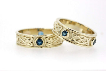 yellow gold celtic design matching his and hers rings, they are set with 3 sapphires in each ring, the 3 stones are rubover or bezel set at north east and west points of the ring