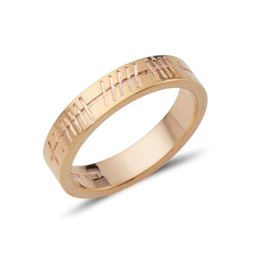 yellow gold flat plain polished wedding ring that is engraved with ogham script
