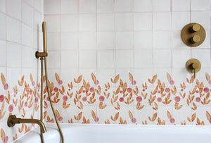 Cherry tile in Rust & Rose by Feild. Handmade and hand painted glazed terracotta tiles. Installed around a bath