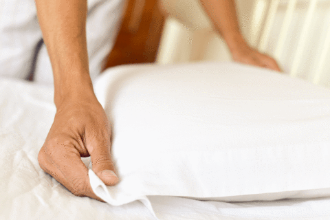 Person Making Bed after Cleaning Pillows